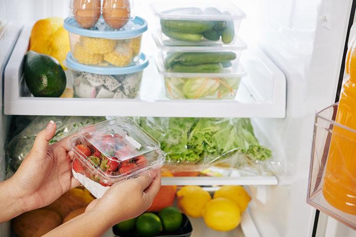 Kobieta wkłada żywność do wypełnionej lodówki